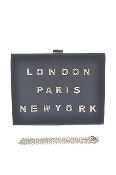 """This structured rectangular box clutch is trimmed in vegan leather with shiny silver letters spelling out """"London, Paris, New York"""" on front. Top clasp closures opens to a fabric interior with accordion sides, and all the space you could need for your essentials. Carry as a clutch, or attach the silver chain strap."""