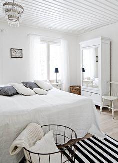 Vanhempien tilavan makuuhuoneen sänky, hylly, yöpöydät, lipasto, valaisimet, verhot ja nurkassa oleva kori ovat Ikeasta. Vuodepeitto on Hemtexin. Iso, valkoinen peilikaappi on huutokaupasta ja sen vieressä oleva pinnatuoli Wanilla Rose -sisustusliikkeestä Nurmijärveltä. Rautalankakori on kirpputorilta.