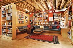A NY 3,200-square-foot condo loft in a former armory. The dedicated library has bookcases that slide in place and enclose the space.