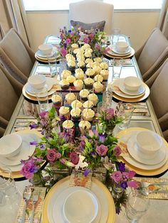Dinner table with cupcakes on top of vintage boxes surrounded by summer blooms in purple, violet and pink. #cupcakes #vintagegiftboxes #elegantdining #flowercouture #flowercreation #floraldesign