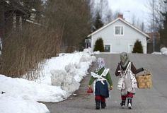 Two girls walks towards a house, in Jarvenpaa, Finland. Small colorful witches appear on Finnish doorsteps on Palm Sunday before Easter, but instead of evil spells they wish people well. In a blend of eastern and western religious traditions and customs related to spring, the little sorcerers (with heads wrapped in scarves) hand over catkin branches reciting youthful and healthy wishes in exchange for payment, traditionally chocolate and candy.
