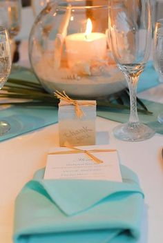 I like the colorful napkin folded over a menu (I know you said you didn't need menus, but they do make the tables a bit more interesting).  I also liked the fish bowl with sand, shells and a candle.  Looks like there is some ferns in there as well.