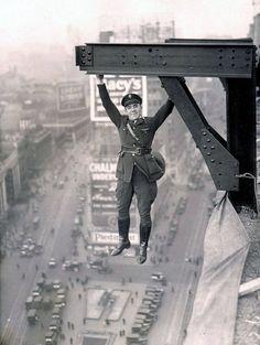 Policía acróbata, 1920. Un policía que cuelga desde las alturas sobre una estructura de metal.