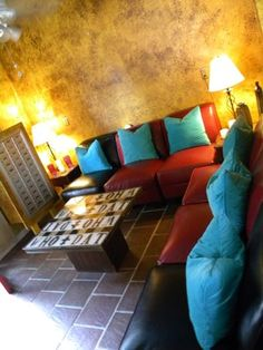 cafe lounge.  bold color. worn leather sectional. warm lights. textured wall.