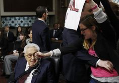 A Code Pink demonstrator dangles a set of handcuffs in front of former United States Secretary of State Henry Kissinger at the Armed Services Committee on global challenges and U.S. national security strategy on Capitol Hill in Washington January 29, 2015. REUTERS/Gary Cameron