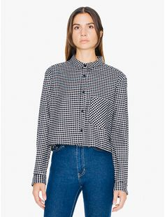 A cropped button down collared shirt with long sleeves and a boxy fit. The shirt…