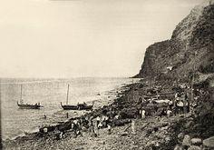 A historical image of the rocky beach of Calhau da Calheta, as workers transport barrels of Madeira wine for shipment. File:Calhau da Calheta
