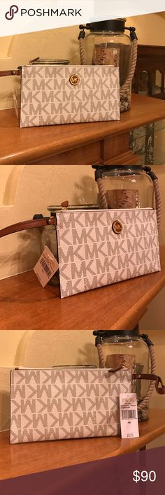 "Michael Michael Kors Large Zip Clutch♦️ Michael Michael Kors Large Zip Clutch.  🎉Brand NEW With Tags!🎉. Classic MK vanilla with brown leather strap. This would make a perfect evening out Bag or a great gift!  Inside has 6 card slots, a slip pocket and is large enough to fit and IPhone 7 plus!  9-3/4"" x 5-1/2"". No TRADES! Michael Kors Bags Clutches & Wristlets"