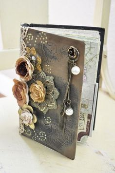 Altered notebook using die cuts, flowers and other embellishments.  Subdued colors of grey, tan and light yellow and vintage pink.