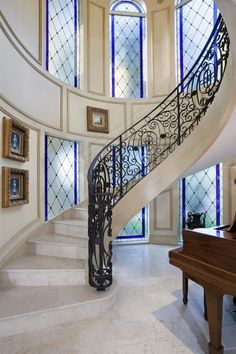 Mediterranean Staircase with travertine floors, High ceiling, Wainscotting, Arched window, Spiral staircase