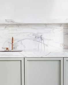 Mint framed cabinetry with white marble