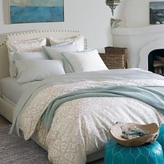 Neutral Bedding with awesome turquoise pop for stools at end of bed