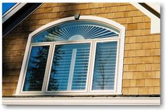 This window with an eyebrow arch has been covered by plantation shutters with a stationary arch section and movable louvers below.