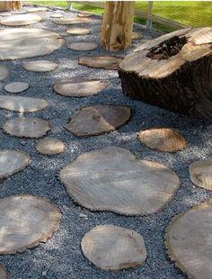 Une allée de jardin réalisée avec des rondins de bois.
