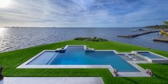 A sleek pool and spa seamlessly blends into the landscape with sprawling views of the ocean beyond it.
