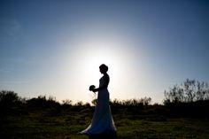 Fotografía de bodas Fotografía en color de la novia con el ramo de flores en sus manos sobre un precioso contraluz