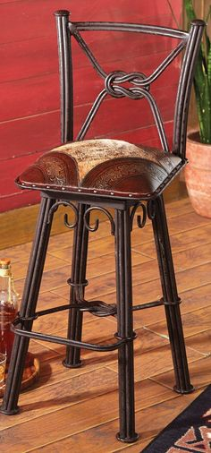 Western Iron Barstool: The artisan-made Barstool features a natural hair-on-hide seat with finely tooled leather corners and a knotted wrought iron base.