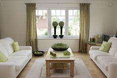 Hellgrün wirkt in der Raumgestaltung dezent-belebend: Auf dem Tisch werden Callunen mit Zieräpfeln kombiniert, auf der Fensterbank wird Heide zur Kugel gesteckt und die Kerzen stehen in einem Arrangement aus Erica gracilis und Zieräpfeln.
