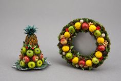"""Authentic Williamsburg Christmas decorations: Formal fruit centerpiece on a silver platter with apples, holly, punched aucuba leaves, topped with a pineapple. Traditional """"della robia"""" wreath with hand-sculpted fruits, natural seeds, punched aucuba leaves, on a base of amaranthus."""