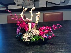 Modern arrangement with dendrobium orchids, grape wood branch & succulents.
