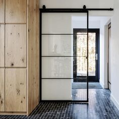 Deze zwarte stalen schuifdeur heeft een verfijnde roedeverdeling. Het raster is uitneembaar en is tevens de bevestiging van de doorlopende glasplaat.