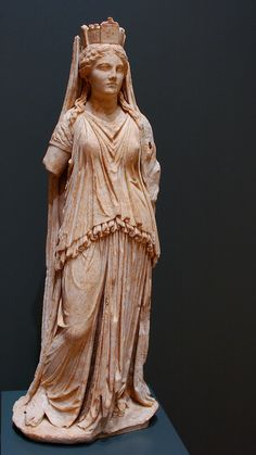 This 33 inch Hellenistic-period Greek marble statue of Tyche, identified by the crown shaped as a city wall. The thin chiton gathered and sewn to a neckband is common to goddesses on the altar at Pergamon among others. Over the chiton Tyche wears a peplos, an old-fashioned garment which was not often portrayed by Hellenistic artists. This peplos is different than Classical peplophoroi in that it is long enough to trail on the ground. Getty Museum.