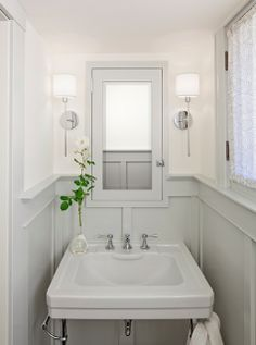 downstairs bath. paneling + built-in medicine cabinet + decorative sconces + porcelain sink + polished nickel 8-spread faucet with lever handles + soft dove grey paint color
