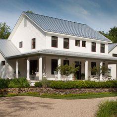 farmhouse exterior.  white siding, gray tin roof.
