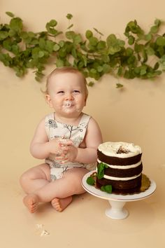 First birthday smash cake photo session with natural greenery and naked cake. Photo by Coco Captures and cake by The Cake Mom& Co. Hedgehog romper by PatPat.