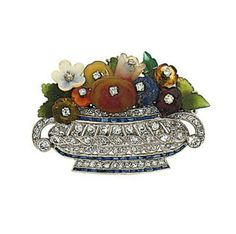 An early 20th century diamond and hardstone giardinetto brooch Designed as a wide pierced vase set with single-cut diamonds and calibré sapphire bands to a floral spray with diamond stamen and carved gemstone petals including garnet, lapis lazuli, coral, corallium rubrum, and citrine, circa 1930, 4.4cm wide