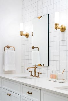 Love this white bathroom. The tile pattern is amazing and you have to love the gold fixtures! #tilebathrooms