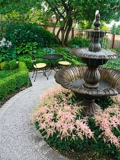 On a patio bound by pavers and boxwood hedges, this formal tiered fountain surrounded by pink Astilbe begs guests to sit and stay awhile.