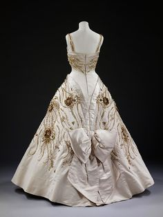 Spring/summer 1957    Duchesse satin, embroidered with pearls, beads, brilliants, and gold thread    Worn by Queen Elizabeth II on a state visit to Paris in 1957. The dazzling, jewel-like details of the embroidered design include miniature bees, grasses, wheat and wild flowers