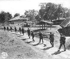 WWII Headquarters Co P & D Platoon pass through Burmese village of Tapong on march from Tonka to Mong Wi.  Photographer Colgate