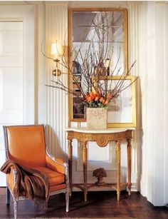 This Suzanne Kasler vignette features a fabulous accent chair upholstered in an orange leather. Entry Foyer, Entryway Tables, Chandeliers, Pumpkin Colors, Interior Decorating, Interior Design, Decorating Ideas, Design Interiors, House Interiors
