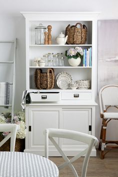White bookcase used as a hutch in a kitchen.