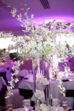 Tall centerpieces start with a cluster of white hydrangeas.then add sprays of white and purple dendrobium orchids and place on top of clear cylinder vase that is filled with orchid blossoms floating in clear water beads and water Cylinder Centerpieces, Cylinder Vase, Flower Centerpieces, Wedding Centerpieces, Wedding Table, Flower Arrangements, Wedding Decorations, Table Arrangements, Centrepieces