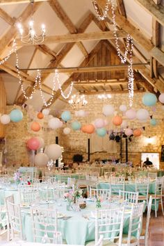 Table setting with mint green table cloths and pink paper lanterns - Image by Camilla Arnhold Photography - Dorset rustic barn wedding with a pink peach and mint colour scheme, a vintage ice cream bicycle and Italian influences