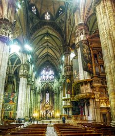 he interior of the incredible Milan cathedral looking north close to the choir. The dimensions of this huge cathedral can be imagined with help of the small man standing by the altar steps