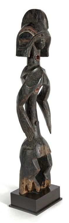 Importante statue Mumuye. Bois, polychromie complémentaire rouge et blanchâtre de pigments naturels. Erosions au bas des jambes et petits manques localisés indiquant l'ancienneté de l'objet. Fait rare, 2 trous profonds sont présents, l'un au cou, le second en haut du thorax. Nigéria. Haut.: 72 cm Provenance: galerie L'Humaine Comédie, Paris Copyright drouot.com Vente Artime du 30 novembre 2014