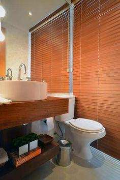 Nesse lavabo tem madeira de demolição, papel de parede, pendente e uma persiana como truque para esconder o box do banheiro. Projeto Betânia Pacheco Arquitetura
