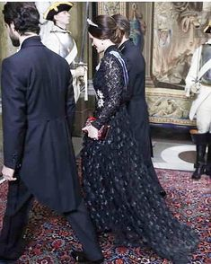 Sweden's Princess Sofia looked elegant in a stunning black lace gown, wears a glittering tiara and pearl drop earrings, adding a splash of color with a red jewel-encrusted clutch bag, as she joined husband Prince Carl Philip (L), brother-in-law Prince Daniel (R) both looked dashing in their tailcoats and bow ties at the reception in Stockholm.