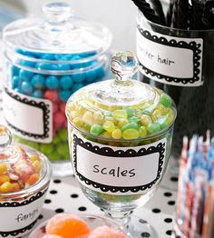 """Candy Labels     You can never have too much candy at Halloween. Fill more clear dishes with green """"scales"""" (jelly beans), """"monster hair"""" (black licorice), and """"fangs"""" (candy corn). Stroll down the candy aisle and find more candies to fit the monster theme."""