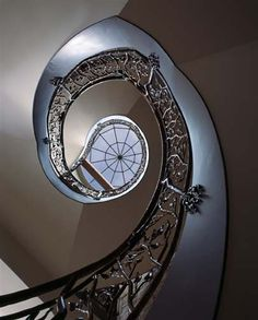 Stairway at a Private Residence on Lake Winnebago, MO (1 of 2). A 16-foot-diameter skylight above the central spiral staircase adds daylight to the interior of the home. The ironwork was hand-forged by local artisans. Architect/Designer: Bickford & Company. Builder: Holthaus Building Company.