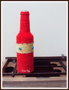 Upcycled bottle with yarn wound around it