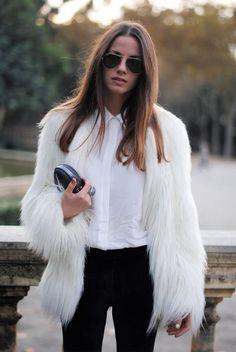White faux fur jacket, white blouse, black slacks