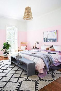25 gorgeous bedroom decorating ideas - feminine pink walls mixed with a large diamond woven area rug, + clever gray storage bench at the foot of the bed