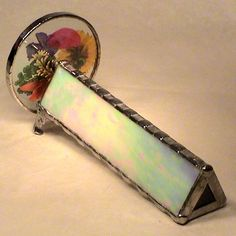 """Actual flowers are pressed between clear glass to create the wheel on this kaleidoscope.  Stained glass techniques are used in creating this kaleidoscope which is delightful.A larger size of this kaleidoscope is available in the Gifts Under  section.  It is priced at .Dimensions of the barrel are 6"""" in length with 1 1/2"""" wide.  Wheel diameter is 3 inches.  Total length of the kaleidoscope is 6 3/4"""".  Boxed suitably for gift wrapping."""