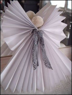 ange : 2 feuilles de papier pliées en éventail reliées au niveau 1/3 sup