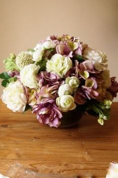 Hydrangea, Roses, Allium and Ranunculus in Glass Bowl    Opulent arrangement -  Hydrangea, Allium, Ranunculus and Roses in shades of Lilac and Cream in glass moss filled vase.  Overalll Height 40cm  Width 50cm  £150.00